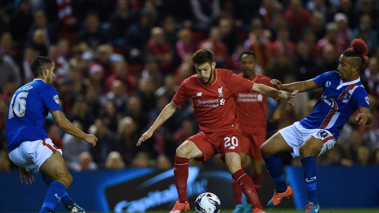Liverpool's Adam Lallana (2nd L) vies with Carlisle United's Gary Dicker and Carlisle United's Bastien Hery (R)