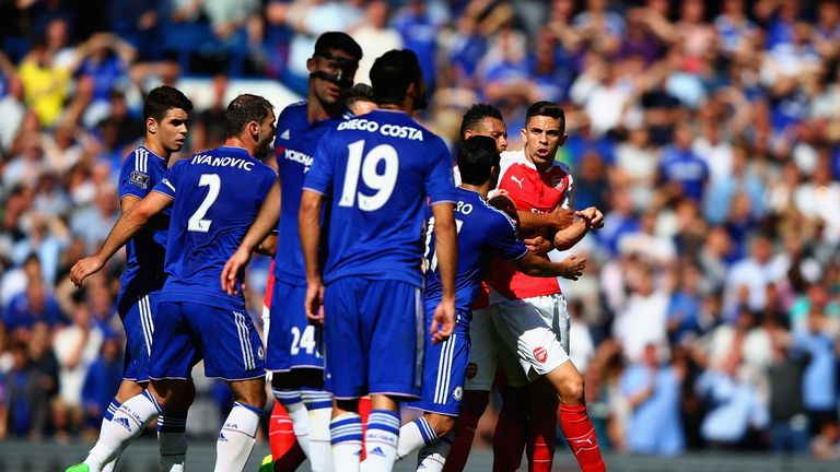 Gabriel is blocked by Chelsea players as he tries to walk toward Diego Costa