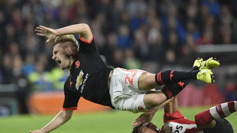 Manchester's defender Luke Shaw (L) is challenged by Eindhoven's Mexican defender Hector Moreno