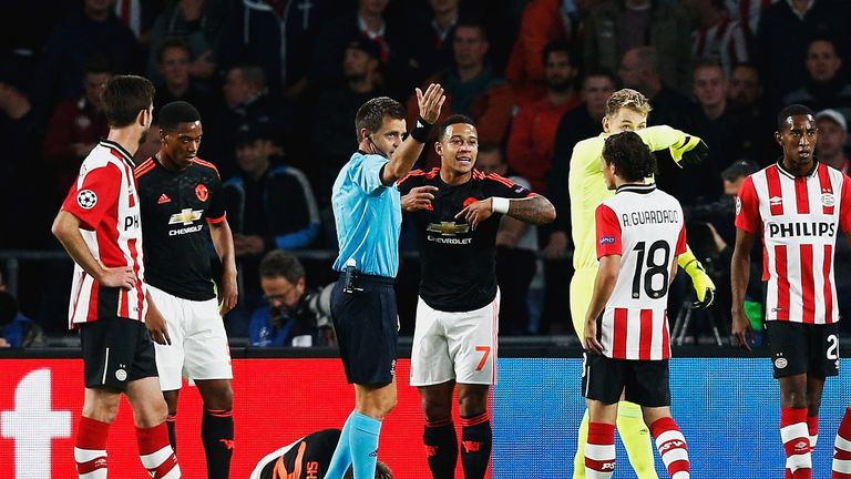 Luke Shaw of Manchester United lies on the ground injured as referee Nicola Rizzoli calls for medical assistance.