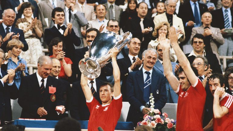 Captain John McGovern lifts the trophy as Larry Lloyd and Frank Clark look on