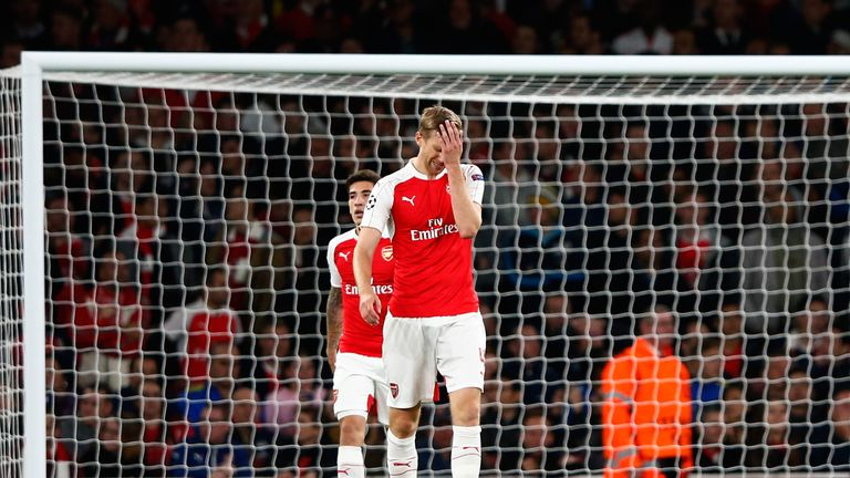 Per Mertesacker can't hide his emotions as Arsenal concede a critical third goal to Olympiakos
