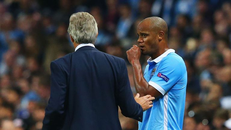 MANCHESTER, ENGLAND - SEPTEMBER 15:  Manuel Pellegrini manager of Manchester City with an injured Vincent Kompany of Manchester City during the  UEFA Champ