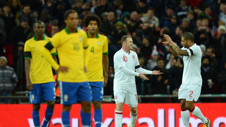 Wayne Rooney of England (back, L) is congratulated by team-mate Glen Johnson of England after he scored the opening goal against Brazil
