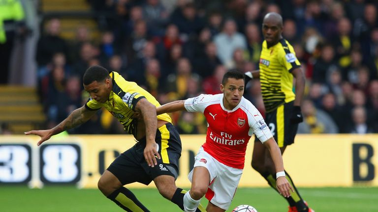 Alexis Sanchez and Troy Deeney compete for the ball