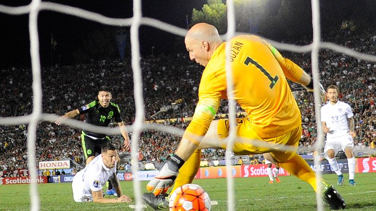 Goalkeeper Brad Guzan #1 of the United States unable to stop a goal by Oribe Peralta #19 of Mexico as teammate Geoff Cameron #20