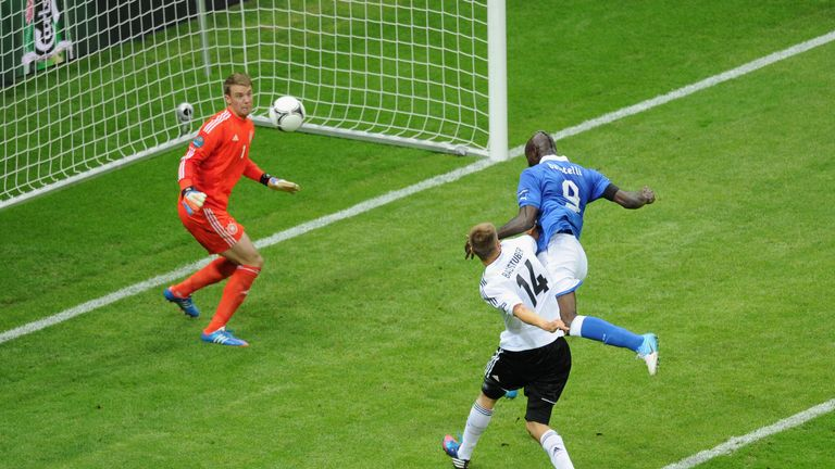 Mario Balotelli (R) of Italy jumps next to Holger Badstuber of Germany to score the opening goal past Manuel Neuer of Germany during Euro 2012 Semi-Final