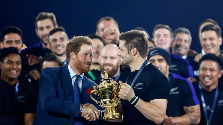 Prince Harry presents Richie McCaw with the trophy after New Zealand became the first country to win the Rugby World Cup three times
