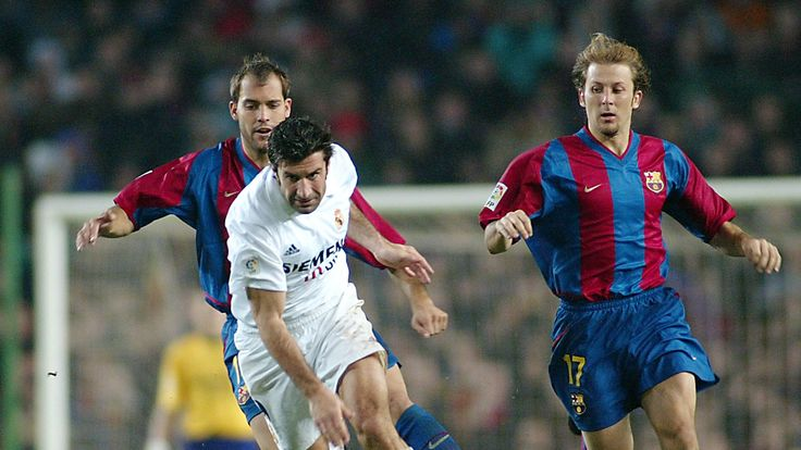 Real Madrid's Luis Figo (C) darts betwen Bacelona's players Gabri (L) and Gaizka Mendieta (R) during their Spanish League match.