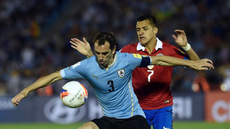 Uruguay's Diego Godin vies for the ball with Sanchez