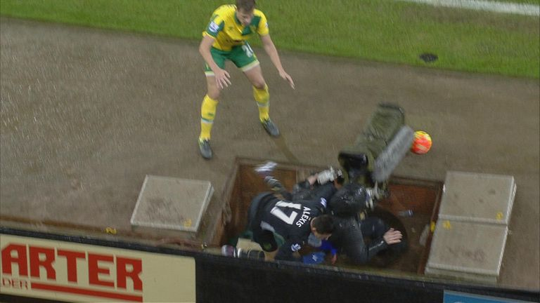 Arsenal's Alexis Sanchez is pushed into the camera pit by Ryan Bennett of Norwich
