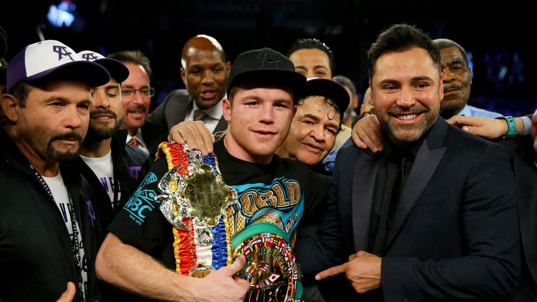 Canelo Alvarez celebrates with promoter Oscar De La Hoya after defeating Miguel Cotto by unanimous decision in their middleweight fight in Las Vegas