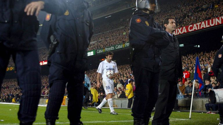 Luis Figo prepares to take a corner with a police escort during the match between Barcelona and Real Madrid.