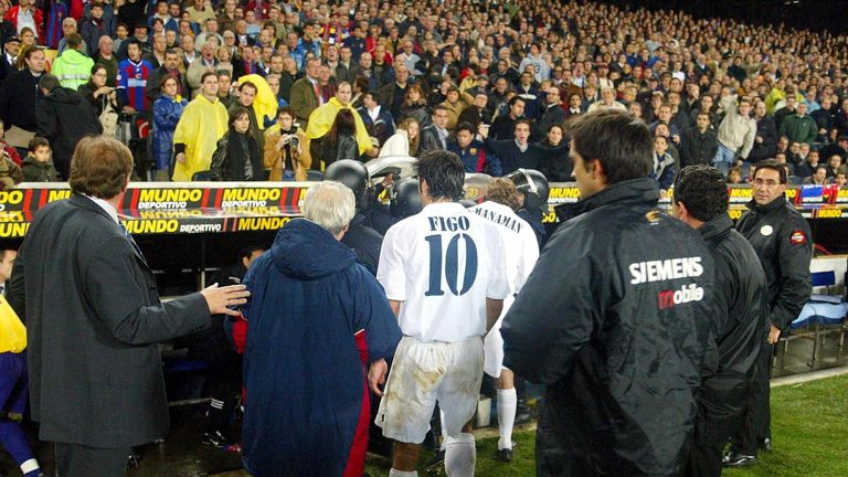 Luis Figo leaves the pitch as play was suspended during the La Liga match between Barcelona and Real Madrid.