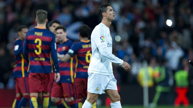 Cristiano Ronaldo of Real Madrid leaves the pitch as Barcelona players celebrate their 4-0 win