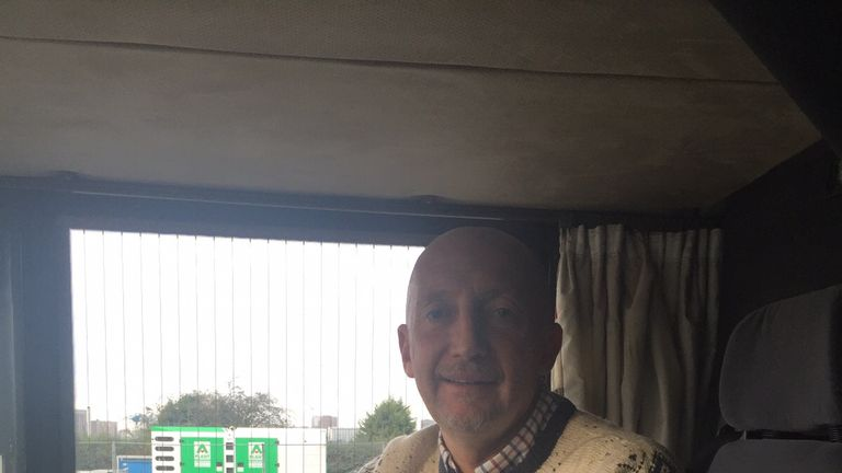 Ian Holloway in the drivers seat of the 10 in 10 bus, complete with a Christmas knit.