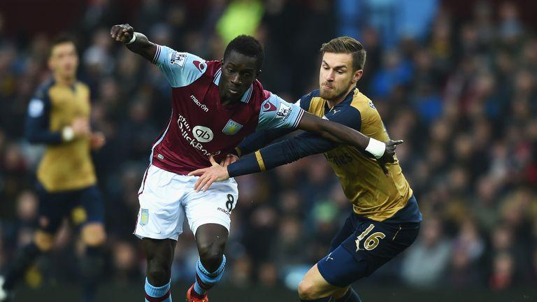 Idrissa Gueye of Aston Villa holds off Arsenal's Aaron Ramsey