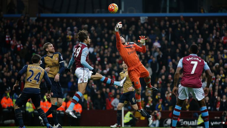 Arsenal's Czech goalkeeper Petr Cech (C) jumps to make a save during the English Premier League football match between Aston Villa