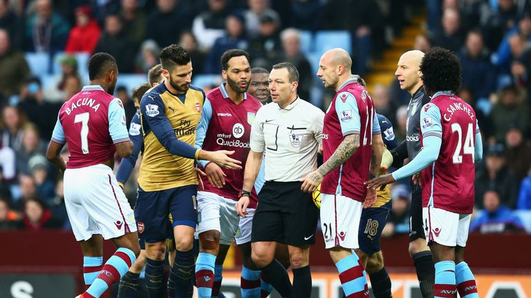 Aston Villa players protest to referee Kevin Friend