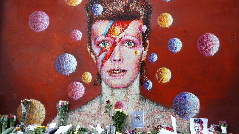 LONDON, ENGLAND - JANUARY 11: Flowers are laid beneath a mural of David Bowie in Brixton on January 11, 2016 in London, England. British music and fashion