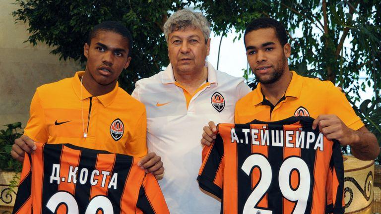 FC Shakhtar head coach Romanian Mircea Lucescu  (C) presents  new players of the team, Brazilian midfielder Douglas Costa  (L) and Alex Teixeira