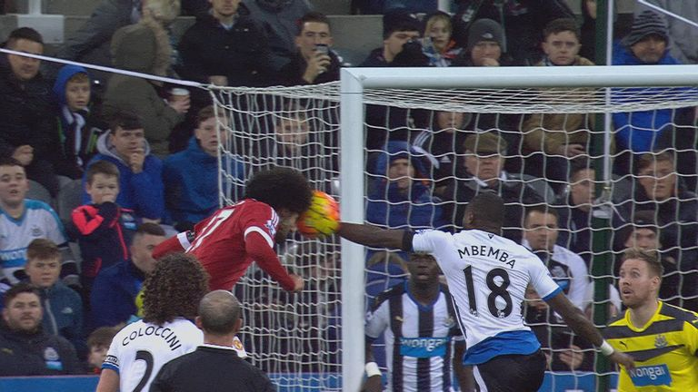 Marouane Fellaini's header is blocked by Chancel Mbemba with his arm
