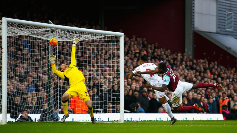 Michail Antonio (R) of West Ham United heads the ball past Liverpool goalkeeper Simon Mignolet (L) to score his team's first goal.