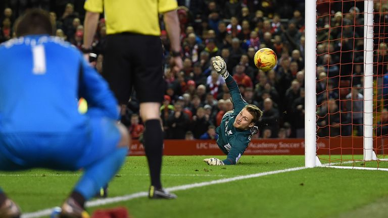 Simon Mignolet of Liverpool saves a penalty during the Capital One Cup semi-final second leg v Stoke City at Anfield