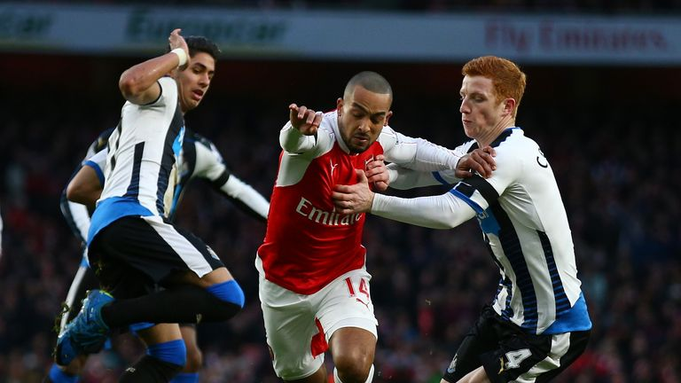 Theo Walcott of Arsenal and Jack Colback of Newcastle United compete for the ball