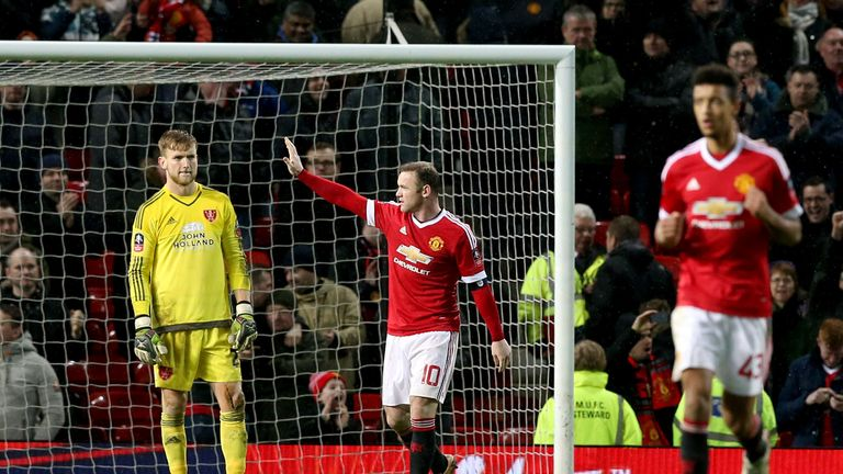 Sheffield United goalkeeper George Long (left) stands dejected as Manchester United's Wayne Rooney (centre) celebrates scoring their first goal of the game