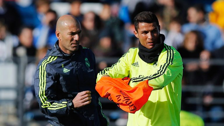 Newly appointed manager of Real Madrid Zinedine Zidane hands a bib to Cristiano Ronaldo during a Real Madrid training session