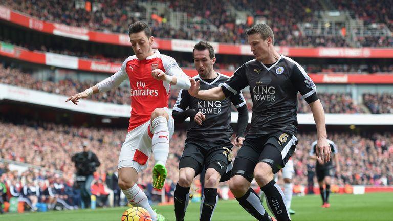Mesut Ozil holds off Robert Huth