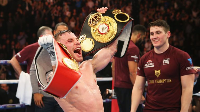 Carl Frampton celebrates with the WBA and IBF belts after his victory over Scott Quigg