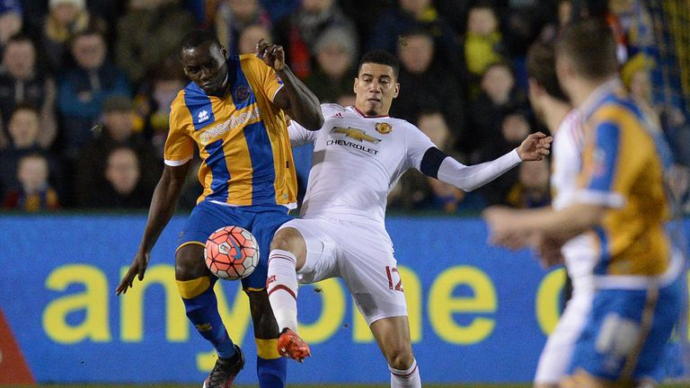 Shrewsbury Town's English defender Jermaine Grandison vies with Manchester United's English defender Chris Smalling