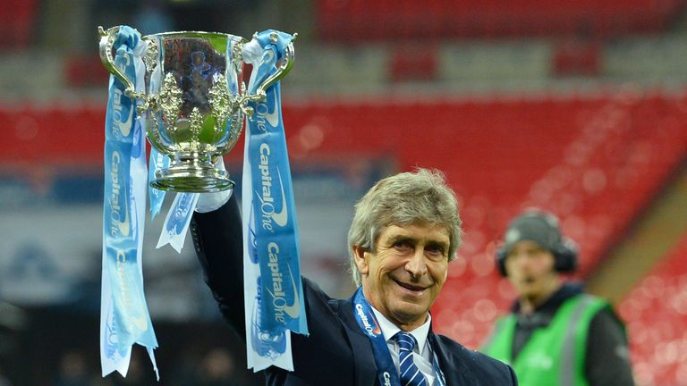 Man City manager Manuel Pellegrini holds up the Capital One Cup