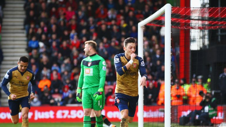 Goalkeeper Artur Boruc of Bournemouth looks dejected as Mesut Ozil of Arsenal celebrates as he scores their first goal