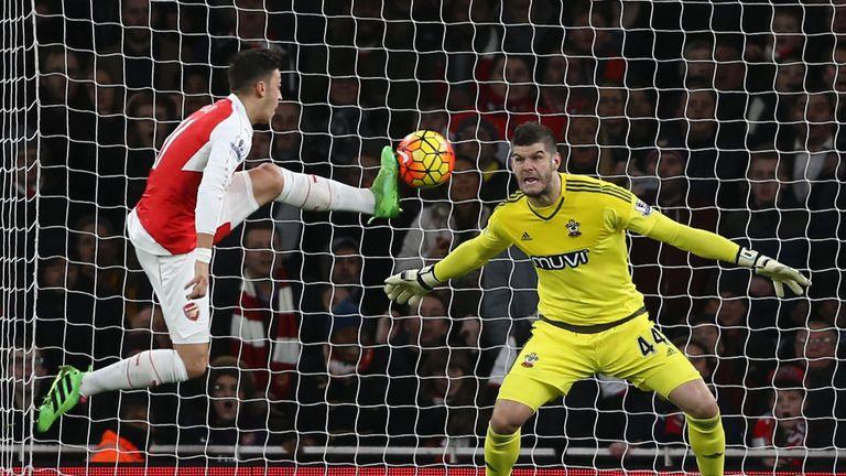 Arsenal's Mesut Ozil (L) leaps in an effort on goal as Southampton's Fraser Forster (R) defends