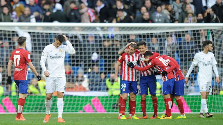 Cristiano Ronaldo of Real Madrid walks away from celebrating Atletico Madrid players after Atletico beat Real 1-0 in the La Liga