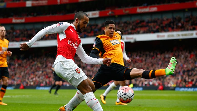 Theo Walcott and Curtis Davies compete in the first half