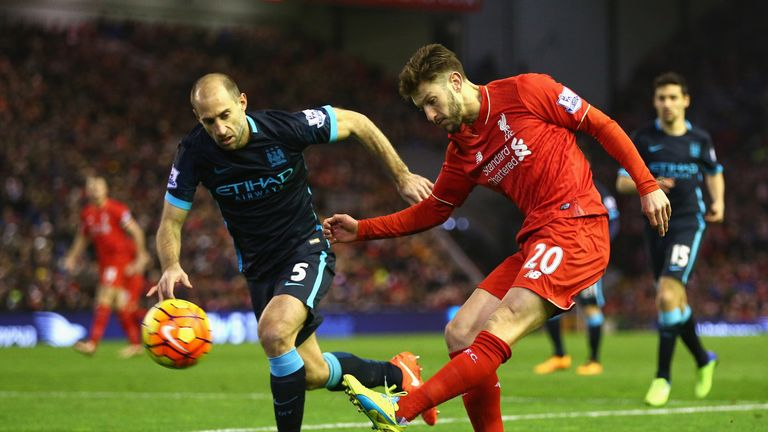 Adam Lallana of Liverpool crosses the ball under pressure from Pablo Zabaleta
