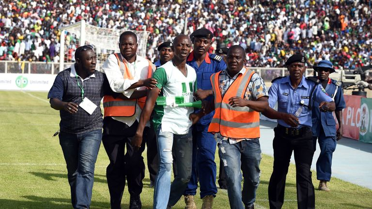 Security officials remove a man who tried to hug Nigerian players during the African Cup of Nations qualification match against Egypt
