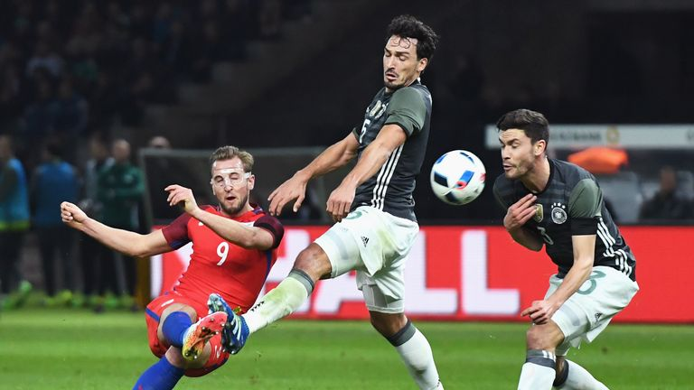 Harry Kane (left) of England shoots at goal while Mats Hummels (centre) and Jonas Hector (right) try to block