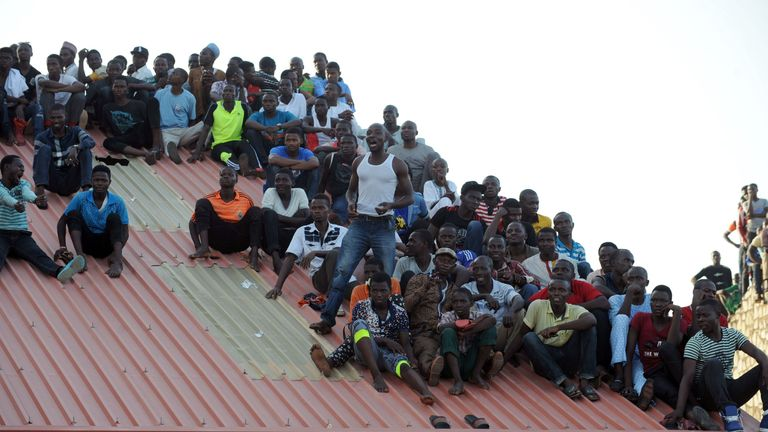 Supporters sit on the roof of a house to watch the African Cup of Nations qualification match between Egypt and Nigeria
