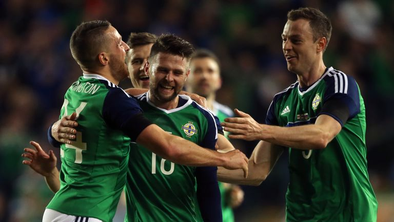 Northern Ireland's Conor Washington (left) celebrates scoring his side's first goal of the game with team mates Oliver Norwood and Jonathan Evans