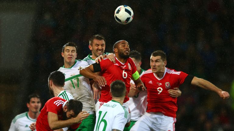 Ashley Williams of Wales heads the ball clear under pressure from Northern Ireland's Paddy McNair