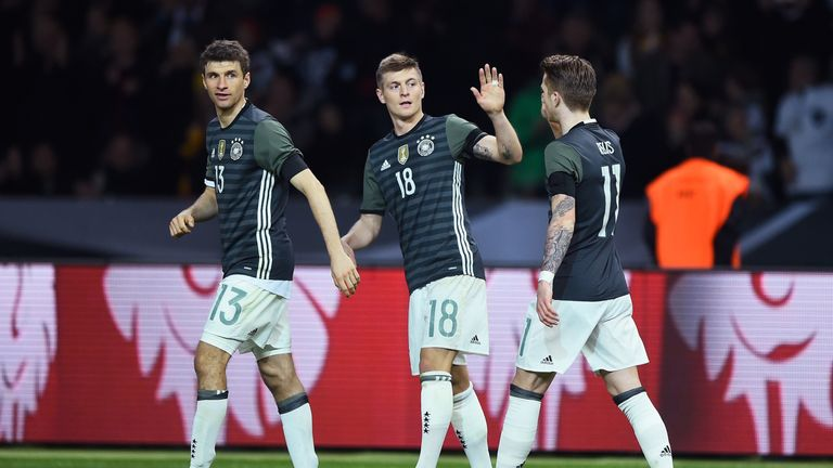 Toni Kroos (C) of Germany celebrates scoring his team's first goal with his team mate Thomas Muller and Marco Reus