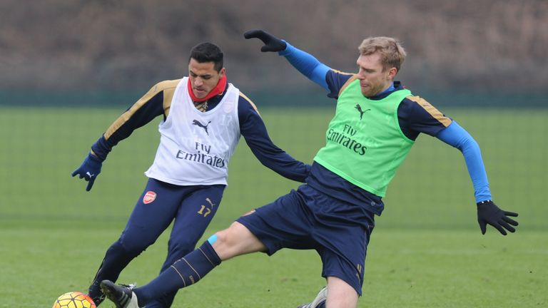 Alexis Sanchez is challenged by Per Mertesacker during an Arsenal training session at London Colney