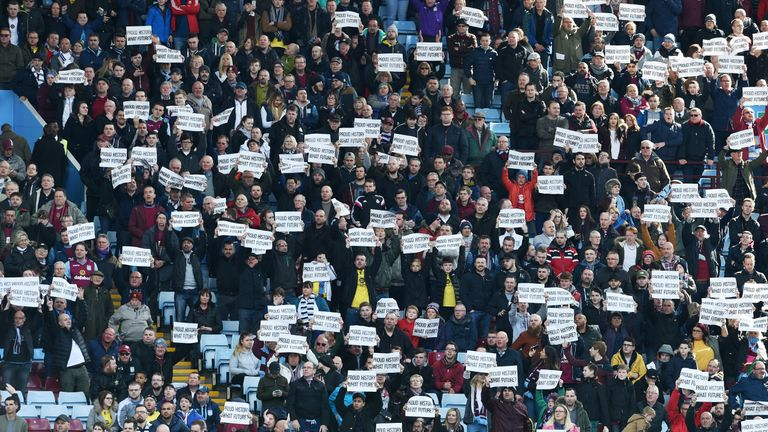 Aston Villa supporters hold protesting banners