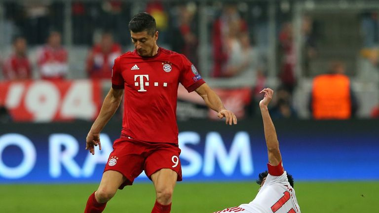 Robert Lewandowski of Bayern Munich is tackled by Nicolas Gaitan of Benfica during the U