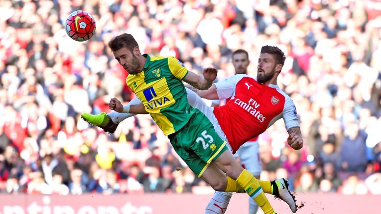 Ivo Pinto of Norwich City clears the ball in front of Olivier Giroud of Arsenal during the Premier League match at the Emirates